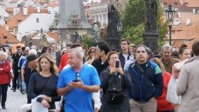 Folkmassa av folk som promenerar Charles Bridge, Prague, Tjeckien långsam rörelse arkivfilmer