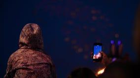 Folkmassa av folkkonturn som h?ller ?gonen p? f?rgrik fantastisk fyrverkerishow i m?rkret arkivfilmer