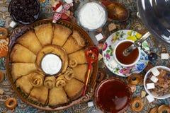 Folkmassa för rund form av pannkakor, honung, te, driftstopp, socker och bageln royaltyfria bilder