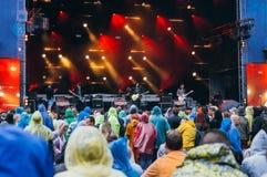 Folkmassa i regnrockar under festivalpreformance Fotografering för Bildbyråer