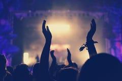 Folkmassa med armar som är utsträckta på konserten Arkivfoto