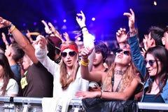 Folkmassa med lyftta armar på en levande konsert arkivfoto