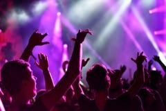 Folkmassa med lyftta armar på en levande konsert arkivfoton