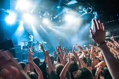 Folkmassa med lyftta nands under konsert royaltyfri bild
