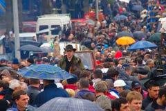 Folkmassa på bymässa på regnig dag Arkivfoto