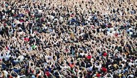 Folkmassa på en musikkonsert, åhörare som lyfter upp händer royaltyfria foton