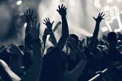 Folkmassa på en musikkonsert, åhörare som lyfter upp händer, tonat Arkivbilder