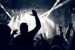 Folkmassa på en musikkonsert, åhörare som lyfter upp händer, tonat Arkivbild