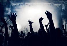 Folkmassa på en musikkonsert, åhörare som lyfter upp händer, tonat Royaltyfri Foto
