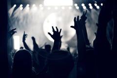 Folkmassa på en musikkonsert, åhörare som lyfter upp händer, tonat Arkivfoto