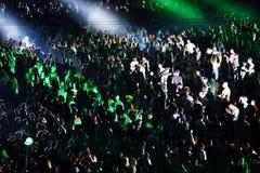 Folkmassa på en musikkonsert, åhörare som lyfter upp händer Arkivfoto
