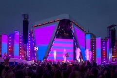 Folkmassa som lyfter deras händer på konserten arkivbild
