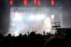 Folkmassa som lyfter deras händer på en konsert Arkivbild