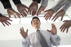 Folkmassa som når för affärsman arkivfoton