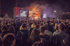 Folkmassa som tycker om det stora festivalpartiet den stora natten för flickor för pojkekonsertfolkmassan ser för att sitta etapp Royaltyfri Foto