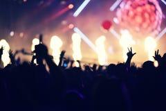 Folkmassa som vaggar under en konsert med lyftta armar Arkivfoto