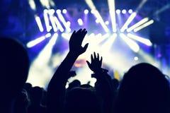 Folkmassa som vaggar under en konsert med lyftta armar Arkivbild