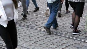Folkmassan av folk korsar vägen En sikt av foten långsam rörelse stock video