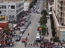 Folkmassan av folk promenerar trottoaren in mot världsserie spelar Fotografering för Bildbyråer