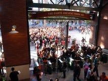 Folkmassan av folk som skriver in AT&T, parkerar Royaltyfria Bilder