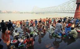 Folkmassan av hinduiskt vallfärdar monterar på packar ihop av floden och ber för sena förfäder Arkivfoton