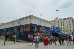 Folkmassan av souvenir shoppar i mycket slående byggnader på strandpromenaden av Santa Monica Juli 04, 2017 Lopparkitektur Holi Fotografering för Bildbyråer