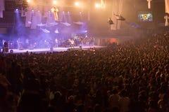Folkmassan på konserten och suddiga etappljus, oväsen tillfogade senare in Royaltyfria Bilder