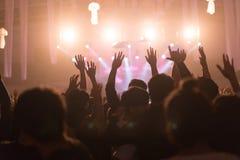 Folkmassan på konserten och suddiga etappljus, oväsen tillfogade senare in Royaltyfri Bild