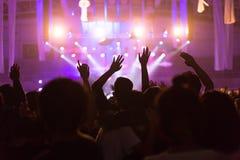 Folkmassan på konserten och suddiga etappljus, oväsen tillfogade senare in Royaltyfria Foton