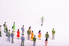 Folkmassan ser mannen som kommer in mot henne på en vit bakgrund Mannen att närma sig en grupp människor Ledare av t Fotografering för Bildbyråer