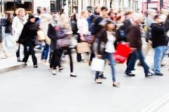 Folkmassor av folk som korsar gatan Arkivfoto