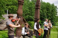 Folkmusik för lek för pojkelandsmusikband med instrument Arkivbild