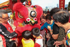 Folks getting goodies from lion dance ritual. KUALA LUMPUR, MALAYSIA- FEB 9, 2014 : Youngs and olds taking goodies from lion dance as a gesture of good luck at royalty free stock photo