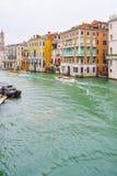 Folksegelb?tar och vattentaxi bredvid gotiska Venetian byggnader p? en regnig November dag p? den Grand Canal vattenv?gen, Venedi arkivbilder