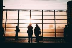 Folksolnedgångkontur - två flickor royaltyfri foto