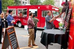 Folkställning i linjen som beställer mål från matlastbilen Arkivfoton
