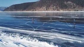 Folkturist att gå för att gå på slät yttersida Pittoreska Lake Baikal knäcker blåa glansiga klara ismindre kulle snöar snödrivor stock video