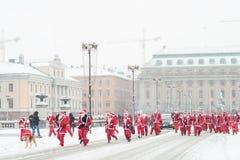 Folkuppklädd som den santas körningen av det svenska parlamenthuset som deltar i välgörenhethändelsen Stockholm Santa Run i Sveri Arkivbild