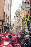 Folkuppklädden som santas kör till och med den gamla staden av Stockholm som deltar i välgörenhethändelsen Stockholm Santa Run i  Fotografering för Bildbyråer