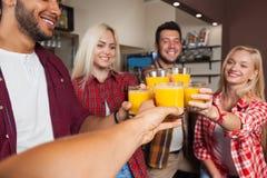 Folkvänner som dricker orange fruktsaft som rostar på stångräknaren, blandningloppmannen och kvinnajubel Arkivbilder