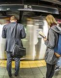 Folkväntan på gångtunnelstationstider kvadrerar i New York arkivfoton