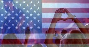 Folla che gode del tempo al concerto con la bandiera americana video d archivio