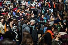 Folla con il cartello, le bandiere ed i segni camminante nelle vie Immagini Stock