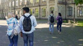 Folla degli studenti che affrettano alla prima classe all'università, vita di mattina dello studente archivi video