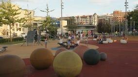 Folla dei bambini divertendosi sul campo da giuoco, vacanze estive, infanzia in grande città archivi video