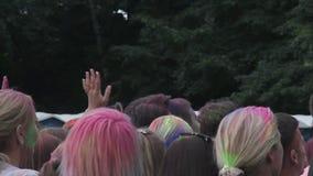 Folla dei giovani coperti in pittura che getta polvere variopinta in aria al fest video d archivio