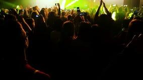 Folla della gente alla luce dei riflettori al concerto stock footage