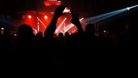 Folla della gente alla luce dei riflettori al concerto archivi video