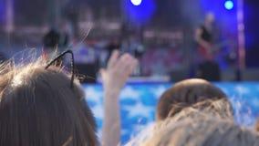 Folla della gente illuminata da luce variopinta durante il concerto archivi video