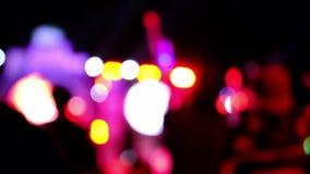 Folla delle siluette della gente con le loro mani su, riflettori di concerto Le luci intense, raggi luminosi della siluetta irrad archivi video